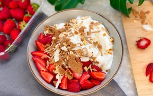 a photo of a yoghurt bowl with carman's goodness & grains cereal on top